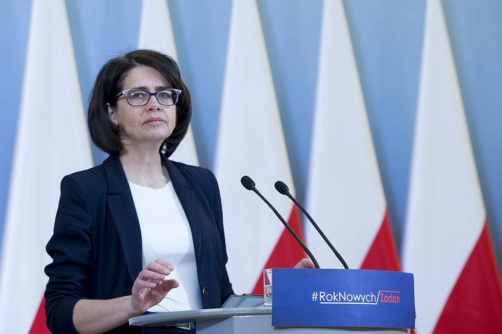 Anna Streżyńska (Minister cyfryzacji) podczas koferencji z01.02.2017 roku. Pani minister stoi przy mówinicy natle polskich flag, anamówincy widnieje napis #RokNowychZadań.